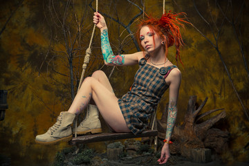 The scenery in the Studio: tattooed redhead girl on a swing in a fantasy forest The conceptual idea
