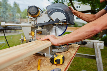 Man using saw to cut wood