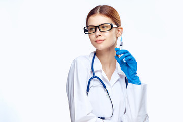 1477972 Young beautiful woman on white isolated background with glasses, doctor holding a syringe