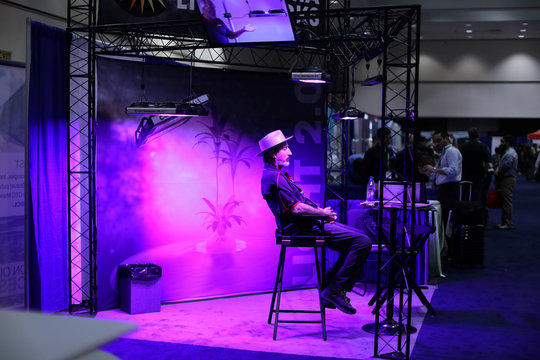 A man sits in a booth advertising lighting for cannabis plants at the Cannabis World Congress and Business Exposition, a trade show for the legalized adult use, medical marijuana and industrial hemp industries, in Los Angeles