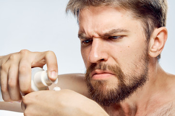 1477982 Man with a beard on a light background applies cosmetic cream, portrait, emotions