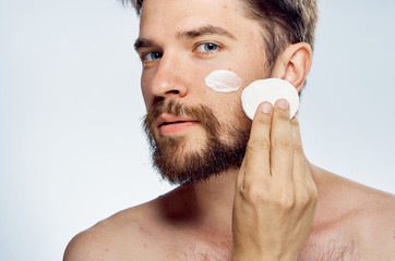 1477986 Man with a beard on a light background, cosmetic face cream, cotton pads, portrait