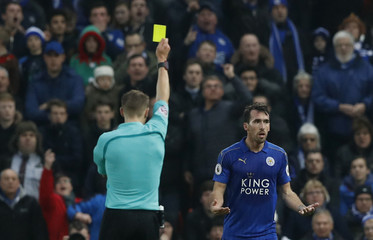 Leicester City's Christian Fuchs is shown a yellow card by referee Craig Pawson