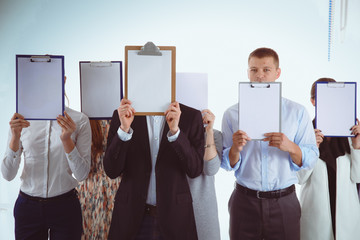 Team of businesspeople holding a folders near face isolated on white background . Businesspeople.