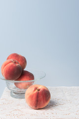 Still life with peaches in a glass bowl on a white lace tablecloth with a blue backdrop.