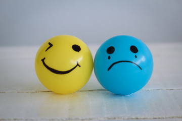 Happy Smiley face ball in yellow and Sadness ball in blue. Self made hand draw balls.
