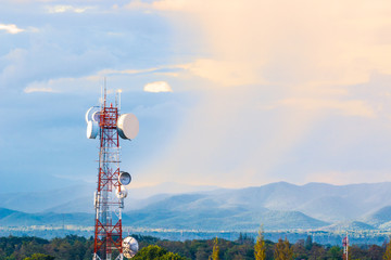 telecommunication tower with mountain range background with warm sunset light casting on clouds Wall mural