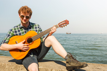 Young man hipster playing guitar by sea ocean.