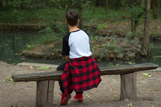 An imaginary boy is sitting on a bench in nature turned back