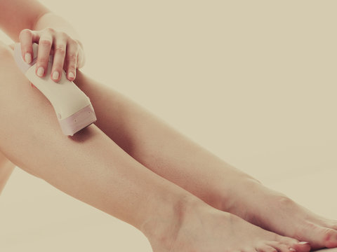 Woman shaving her legs with electric razor