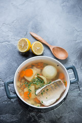 Freshly made sudak fish soup on a grey stone background, vertical shot with space, elevated view