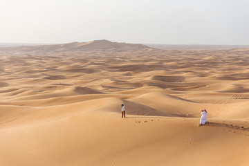 Tourist men, one that wearing thawb are take a photo in the great desert at Dubai.