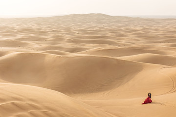 Red costume bride with black suit groom walk together in the great desert in Dubai.