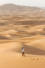 Tourist man take a photo in the great desert at Dubai.