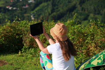 young woman in a hat from the sun takes a photograph with a tablet in the mountains