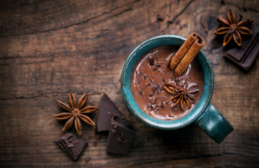 Photo sur Plexiglas Chocolat Hot chocolate in a cup with a cinnamon stick, anise star and dark chocolate flakes on rustic wooden background with an empty tag. Overhead view with copy space for your text
