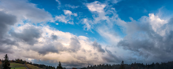 gorgeous cloudscape over the forest on hills. beautiful windy evening in autumnal countryside