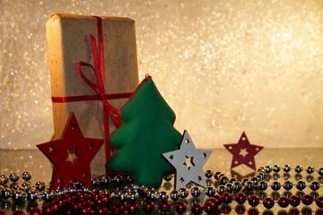 красивый новогодний подарок с красной лентой и елочкой на блестящем белом фоне