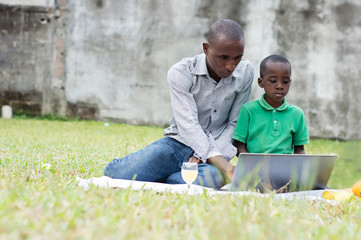 father and son working on a computer outside