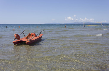 FOLLONICA, ITALY - AUGUST 21 2015: Summer season in Follonica, Tuscany, with lifeboat on the sea and few person