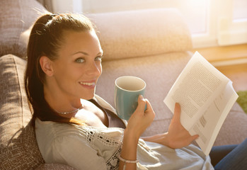 Girl reading book and drinking coffee on sofa