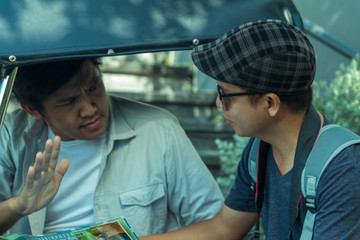 Asian travel photographer negotiates price with tuk tuk driver before traveling around Bangkok Landmark Thailand.