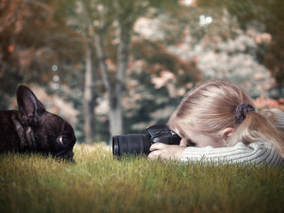 Little girl photographing a dog