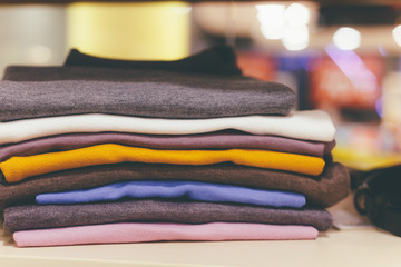 Color sweaters lie a pile on the shelf in the shop