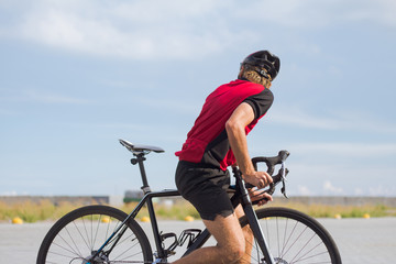 Professional bicycle rider in helmet and sportswear training on empty road