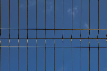 close up picture of cage fence against blue sky