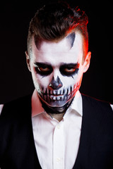Red lights on man with creative make-up for the Halloween party.
