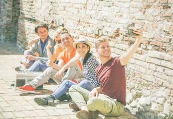 Group of multiracial friends taking a selfie with a mobile smartphone camera