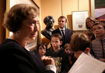 French President Emmanuel Macron stands next to a bust of author Alexandre Dumas as he looks on with schoolchildren and French Minister of Culture Francoise Nyssen as a guide speaks during a visit to the Chateau de Monte-Cristo at Marly-le-