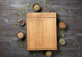 Composition with wooden board, spices and herbs on table