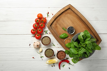 Composition with wooden plate and ingredients for cooking on table