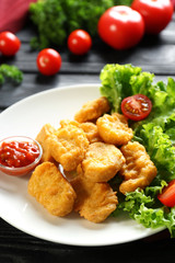 Tasty nuggets and small bowl with sauce for chicken on plate