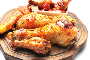Roasted chicken legs in sauce on wooden board, closeup