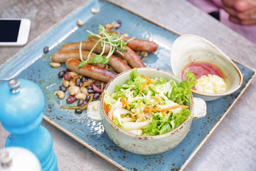 Plate with tasty sausages and salad on table