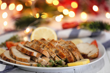 Plate with delicious sliced turkey breast against blurred lights
