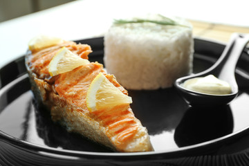 Plate with slice of salmon, rice and delicious sauce on table, closeup