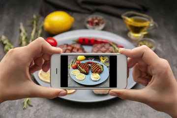 Woman taking photo of yummy grilled steaks at kitchen table