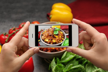 Woman taking photo of yummy stew at kitchen table