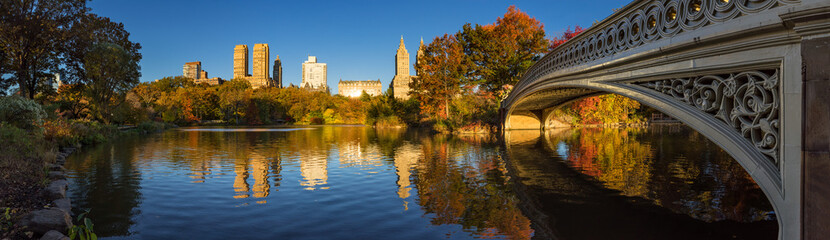 Fall in Central Park at The Lake with the Bow Bridge. Panoramic morning view with colorful autumn foliage on the Upper West Side. Manhattan, New York City