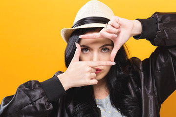 Young woman framing her face with her fingers on a solid background