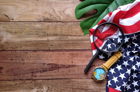 Top view Handkerchief look like USA flag with map watch and Magnifying glass on green leave and wood pattern,  For concept find America on Columbus Day,Have copy space.