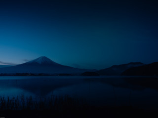landscape view from sunrise and haze on kawaguchi lake with motion blur from group of duck foreground and fuji mountain background with fog from japan
