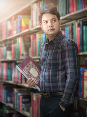 smart young teacher holding book in library,