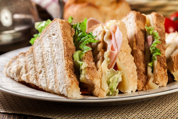 Toasted panini with ham, cheese, salad and tomato sandwich