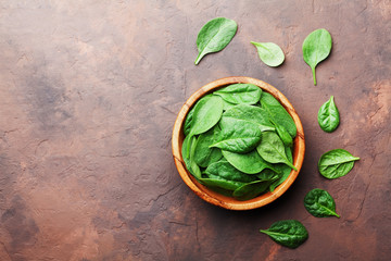 Organic food. Baby spinach leaves in wooden bowl on rustic stone table top view. Copy space for text.