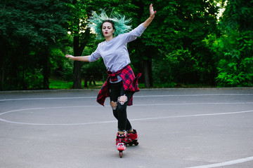 Young stylish funky girl with green hair riding roller skates and dancing in park